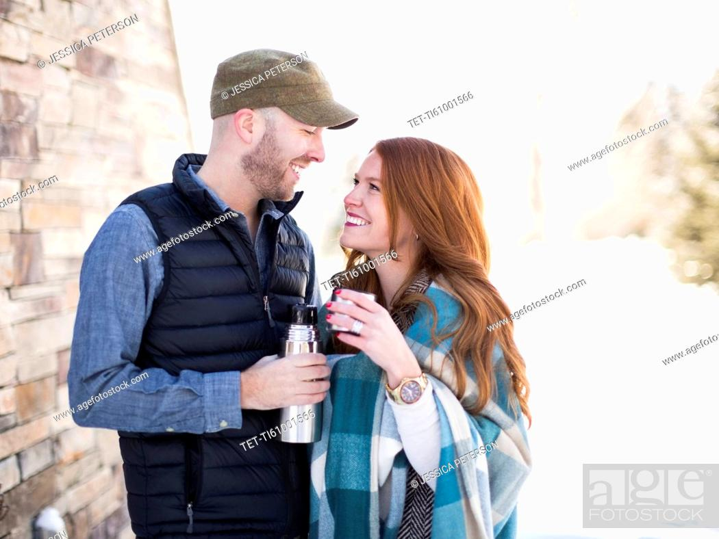 Stock Photo: Mid adult couple looking face to face and having drink from vacuum flask.