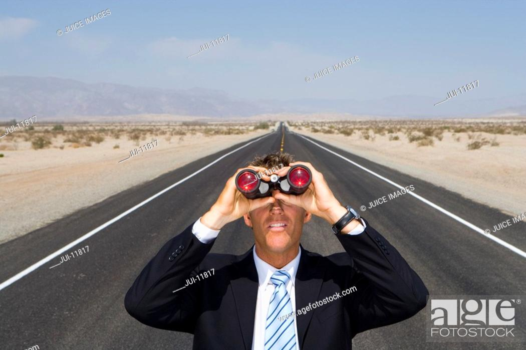 Stock Photo: Businessman in middle of open road in desert, using binoculars, elevated view.