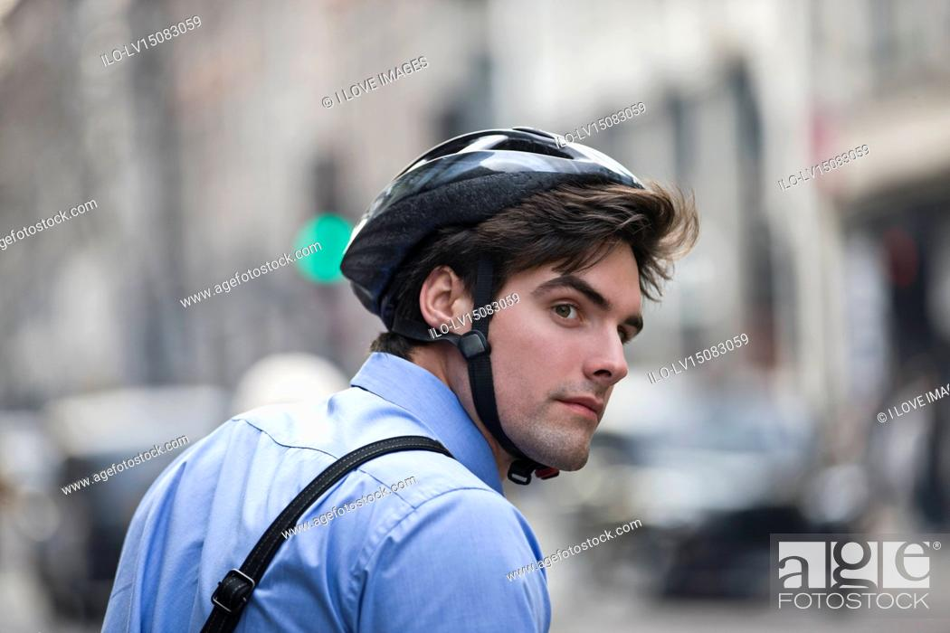 Stock Photo: A businessman wearing a cycling helmet, commuting to work.