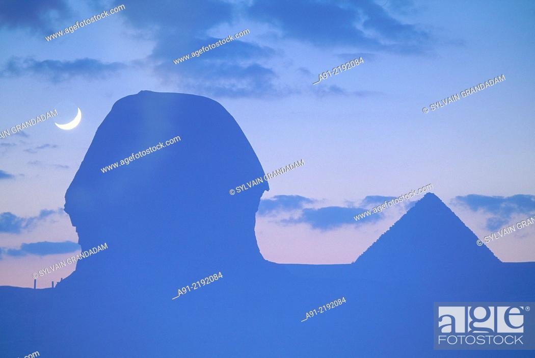Stock Photo: EGYPT.CAIRO.GIZEH.THE SPHINX SILHOUETTE AND PYRAMIDS BACKLIGHTED AT DUSK.