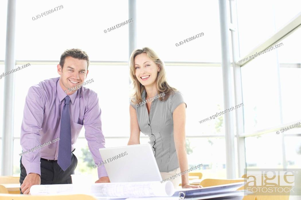 Stock Photo: Businesspeople leaning on desk smiling.