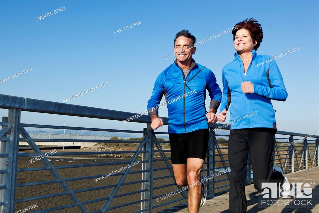 Stock Photo: USA, California, San Francisco, Senior couple jogging on boardwalk.