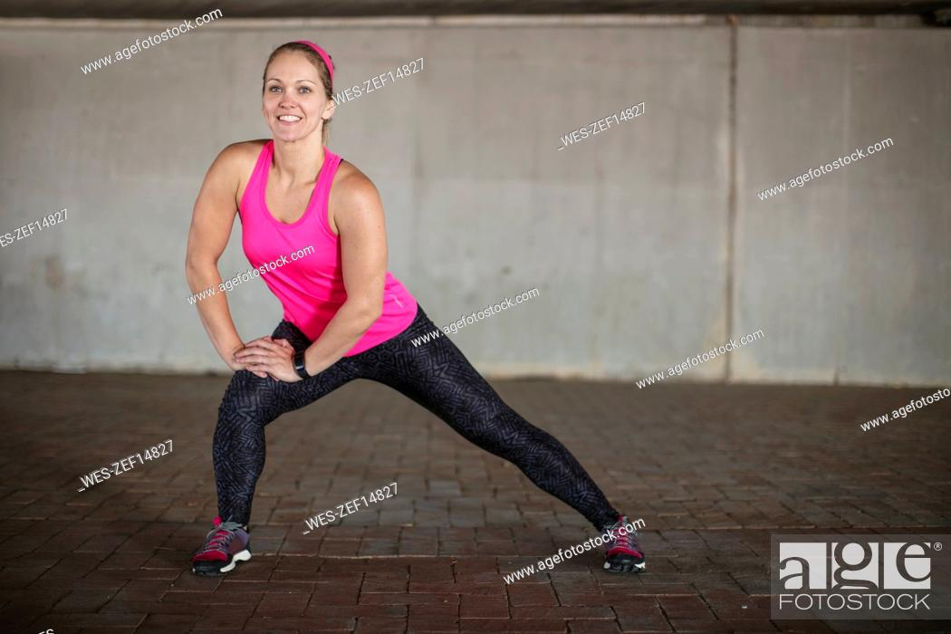 Stock Photo: Smiling sportive woman stretching.