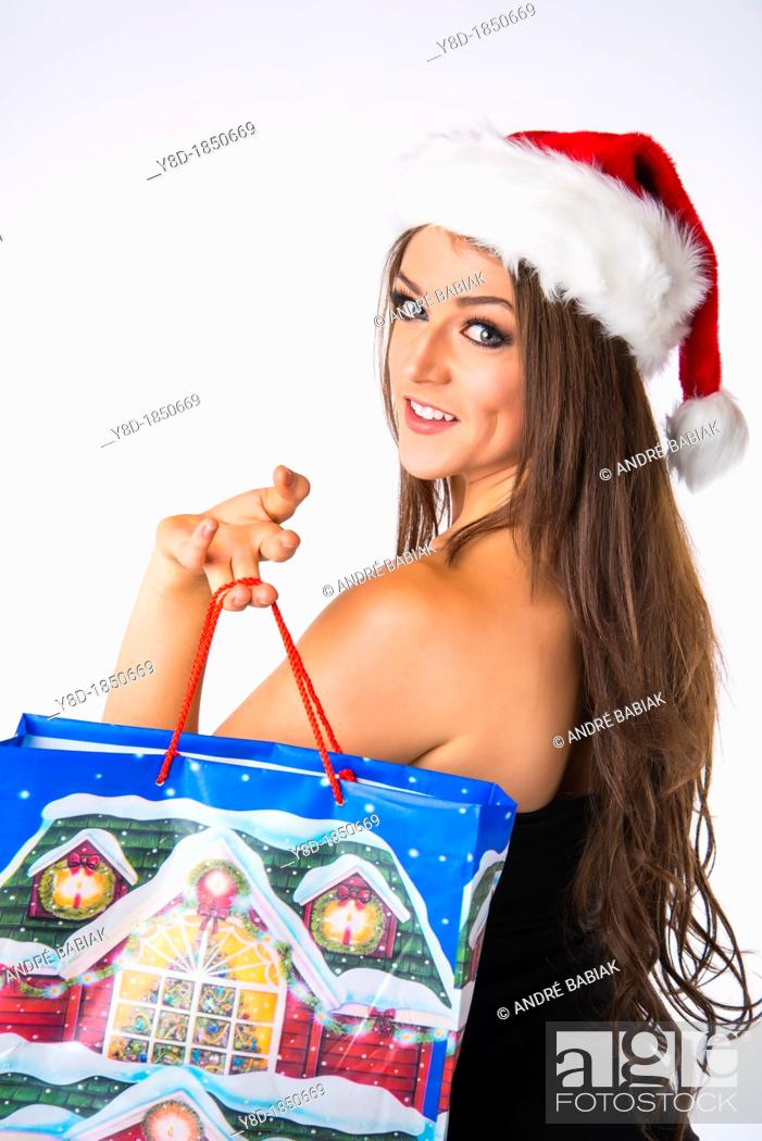 Stock Photo: Young woman, Caucasian, 21 years old, wearing Christmas jelly bag cap while carrying shopping bag.