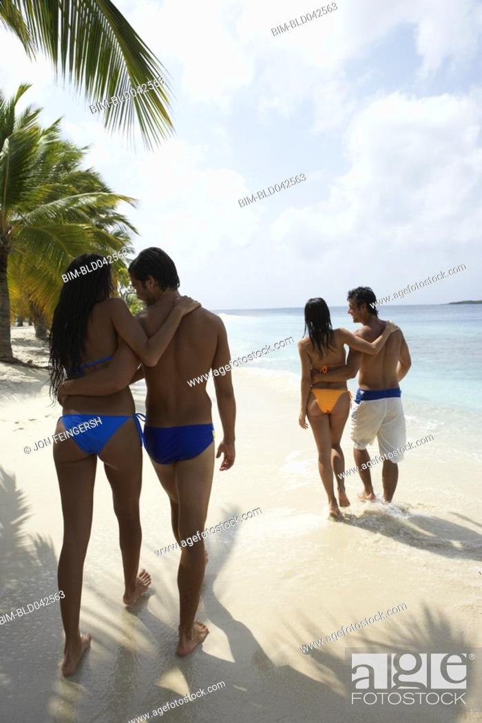 Stock Photo: South American couples walking on beach.