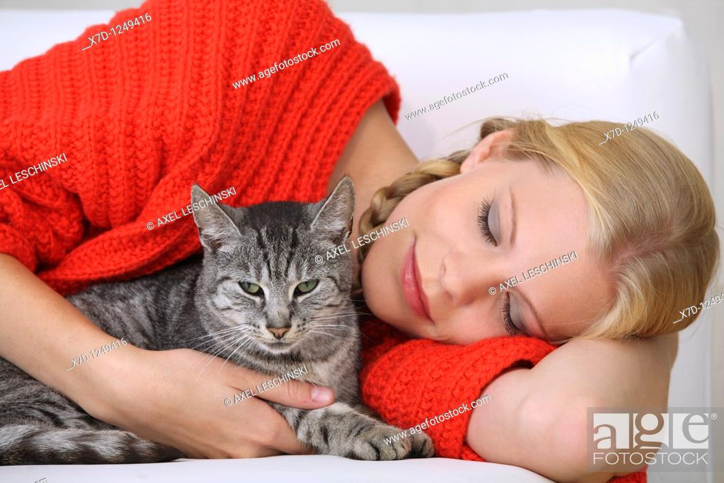 Stock Photo: young blond woman fondling domestic cat.