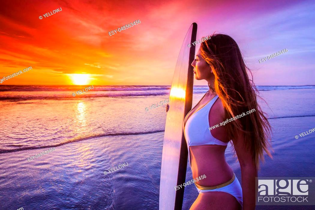 Stock Photo: Beautiful sexy surfer girl on the beach at sunset.