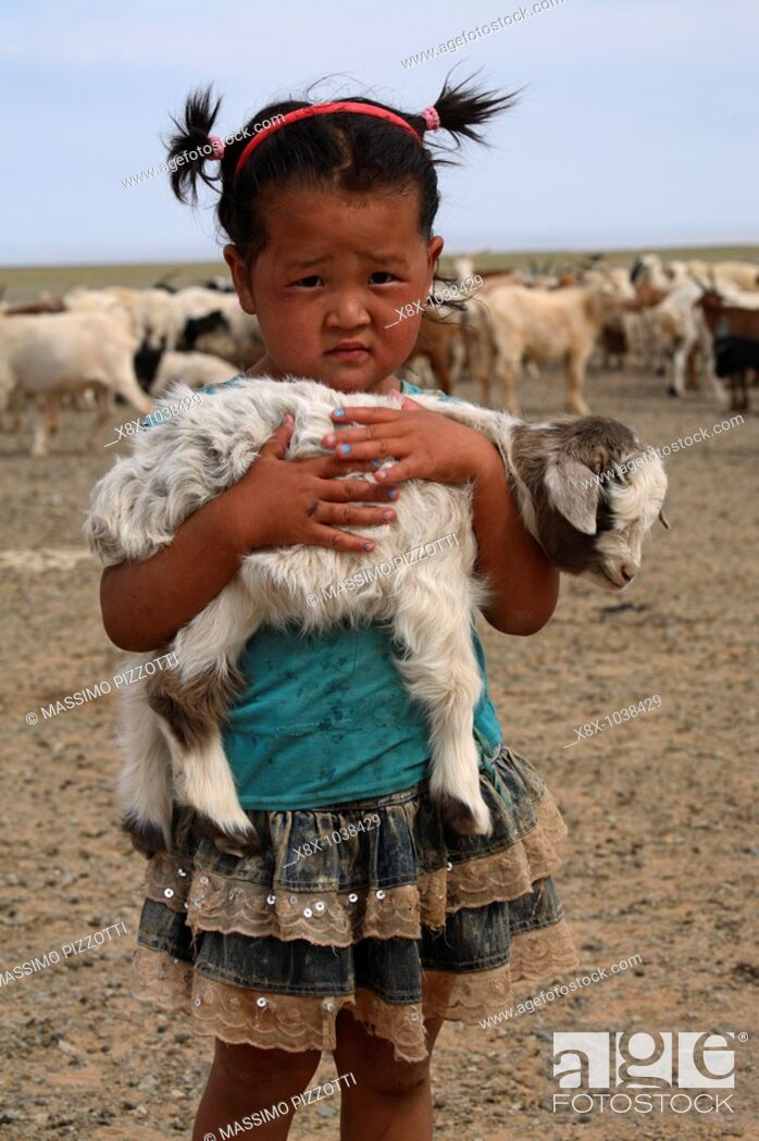 Imagen: Portrait of mongolian little girl holding a lamb in her arms, Mongolia.