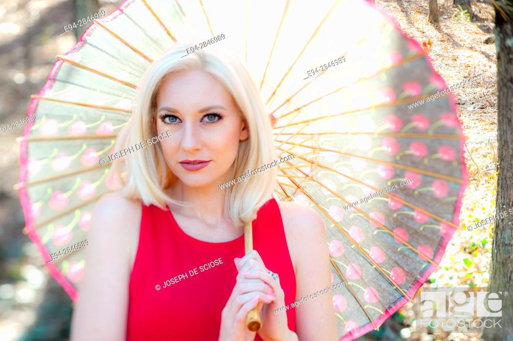 Stock Photo: Portrait of a 30 year old blond woman looking at the camera and holding a parasol on her shoulder, outdoors.