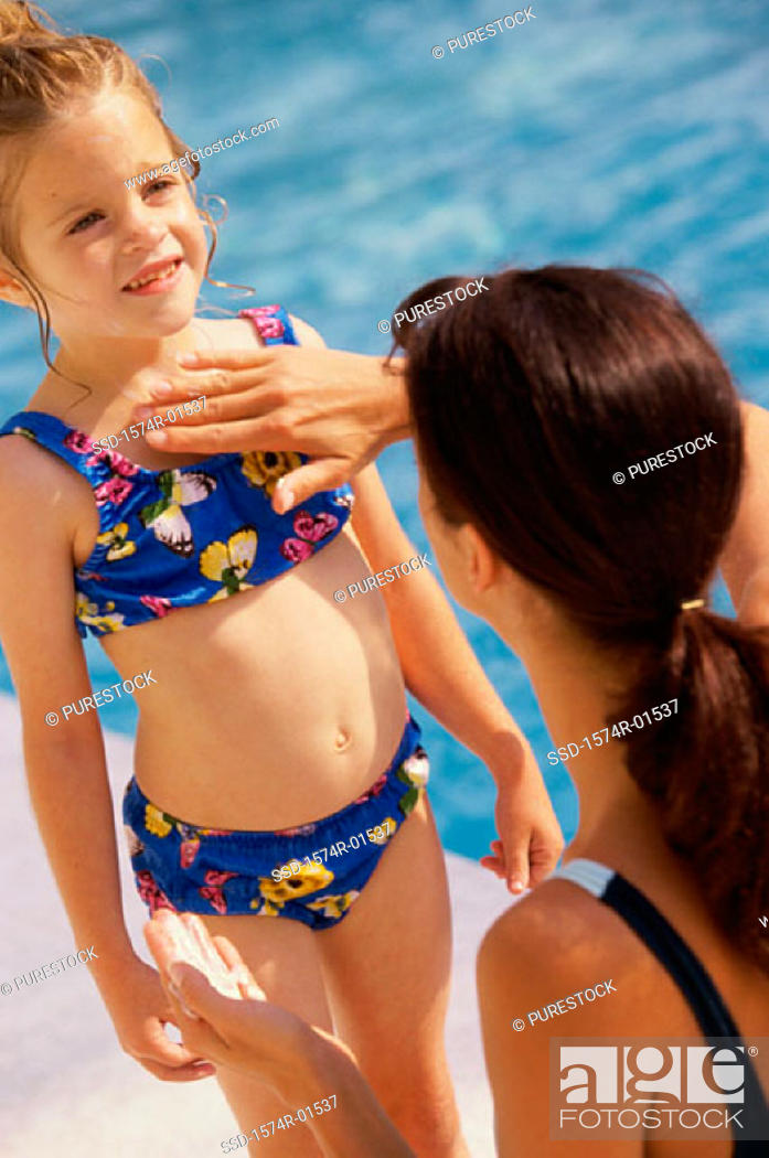 Stock Photo: Woman applying sunscreen lotion on her daughter at a poolside.