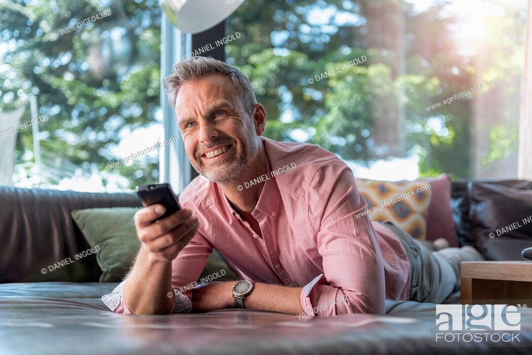 Stock Photo: Smiling mature man lying on couch at home using remote control.