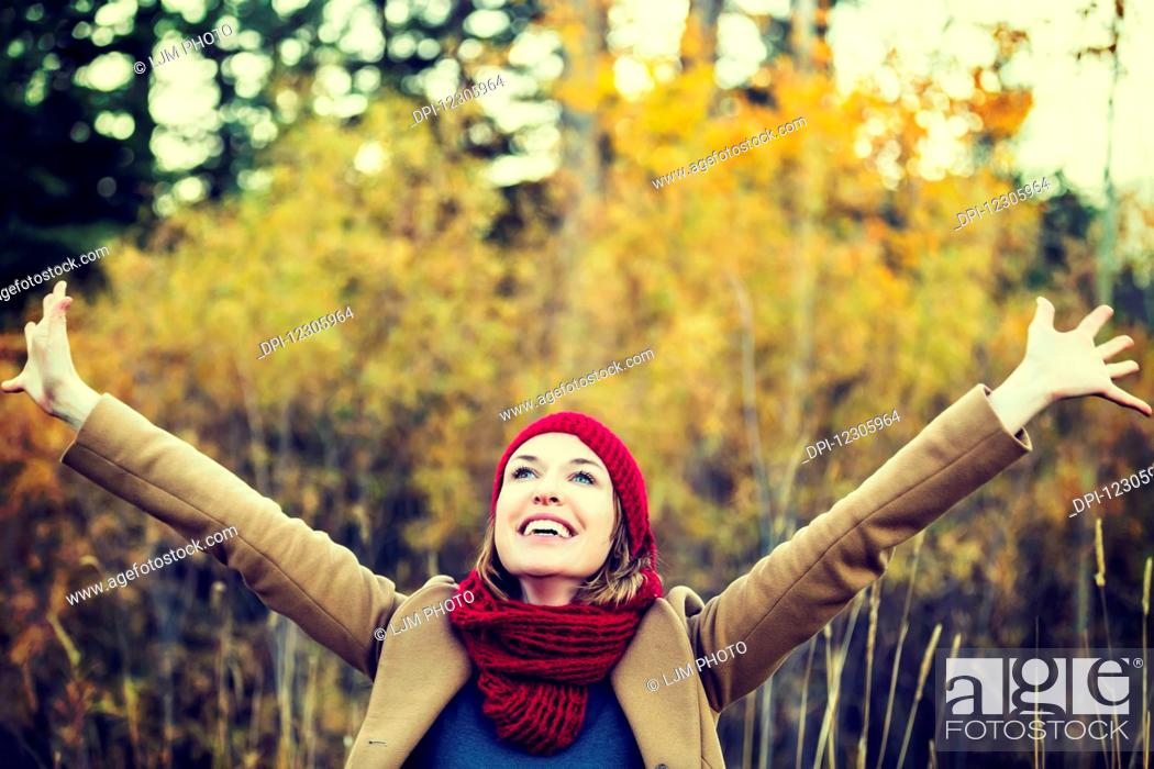 Stock Photo: A beautiful young woman raising her hands in joy during an outing in a park in autumn; Edmonton, Alberta, Canada.