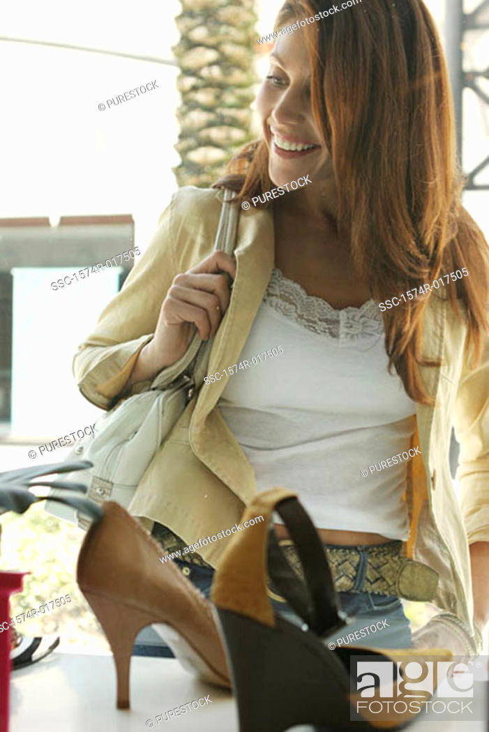 Stock Photo: Young woman looking at shoes in a shoe store.