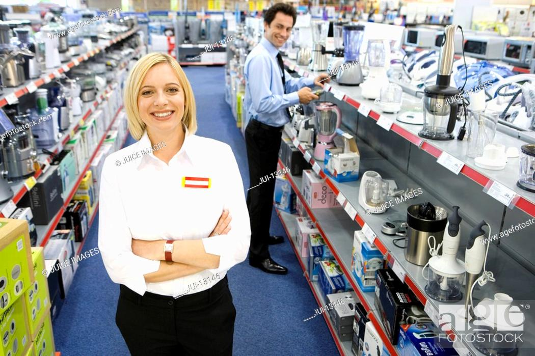 Stock Photo: Young saleswoman in electronics aisle with arms crossed, smiling, porttrait.