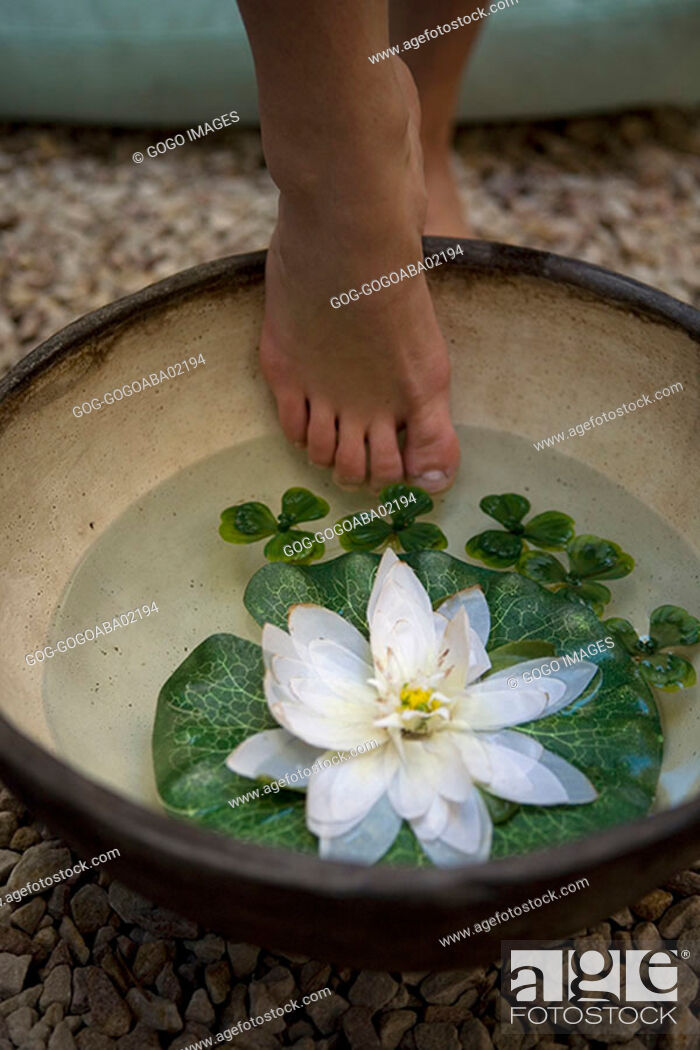 Stock Photo: Woman stepping into bowl of water and water lilies.