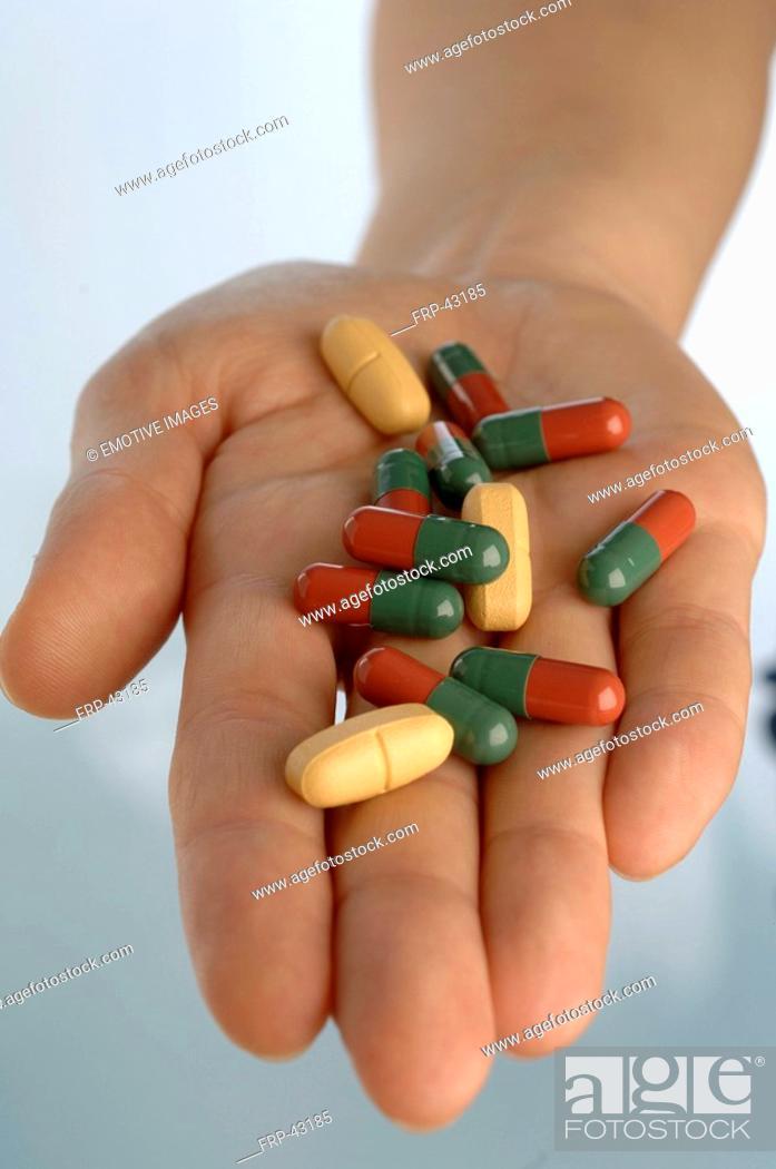 Stock Photo: Hand holding pills.