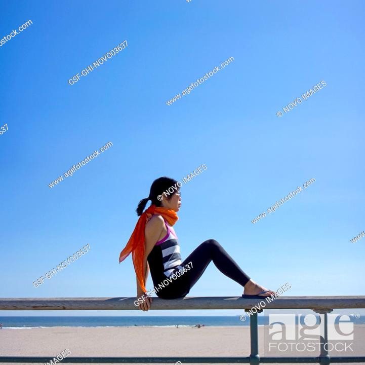 Imagen: Profile View of Woman Sitting on Bench at Beach.