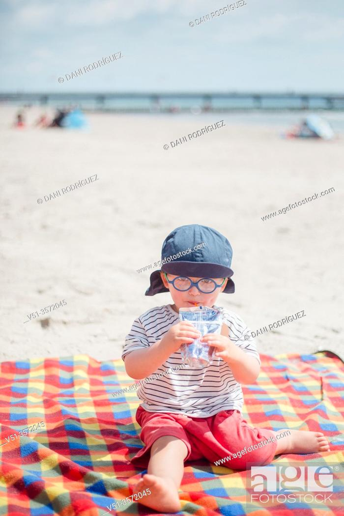 Stock Photo: . 2 years old boy drinking juice at the beach.