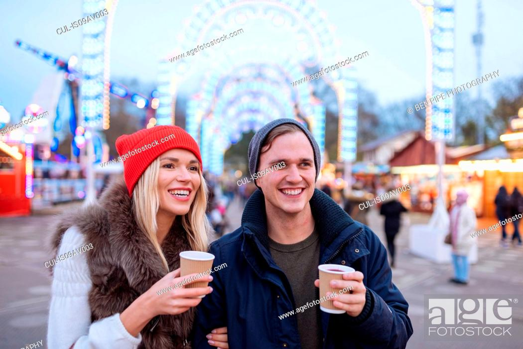 Stock Photo: Happy young couple drinking mulled wine at Xmas festival, Hyde Park, London, UK.