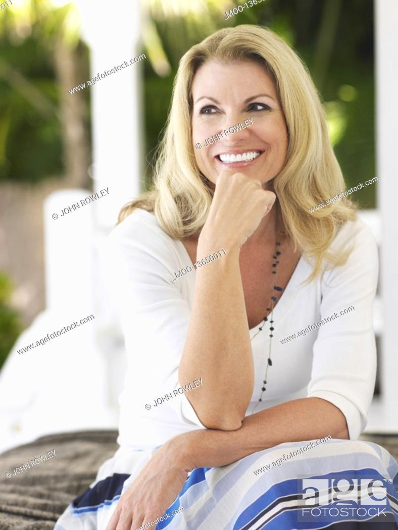Stock Photo: Woman sitting on verandah portrait.