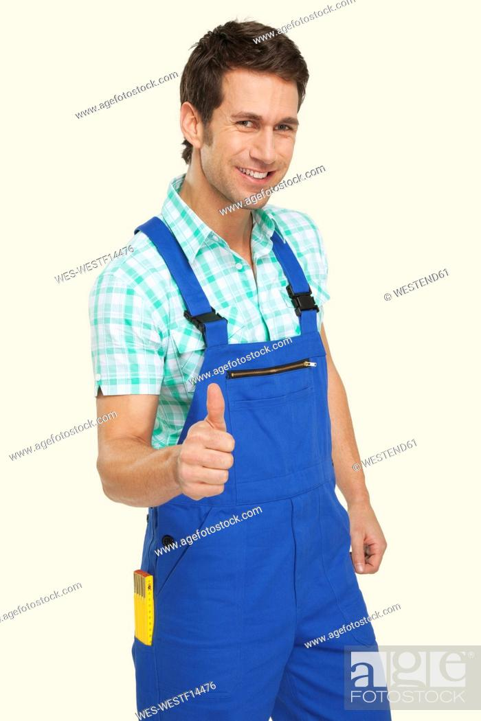 Stock Photo: Man in overall showing thumbs up sign, smiling, portrait.