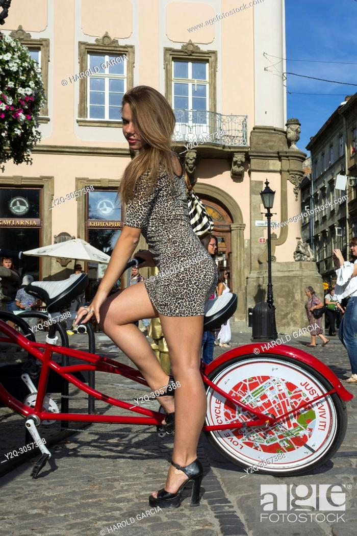 Imagen: Sexy, slim and elegant Ukrainian woman wearing a leopard skin print suit posing on a red and white touring bike for a photographic sequence in the ancient city.