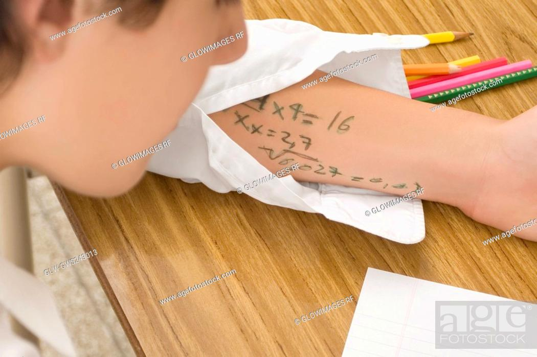 Stock Photo: Close-up of a schoolboy copying in an examination.