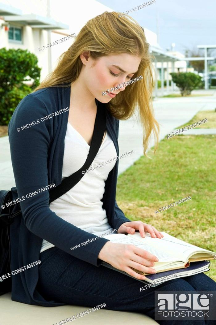 Stock Photo: Female college student sitting on bench reading book on campus.