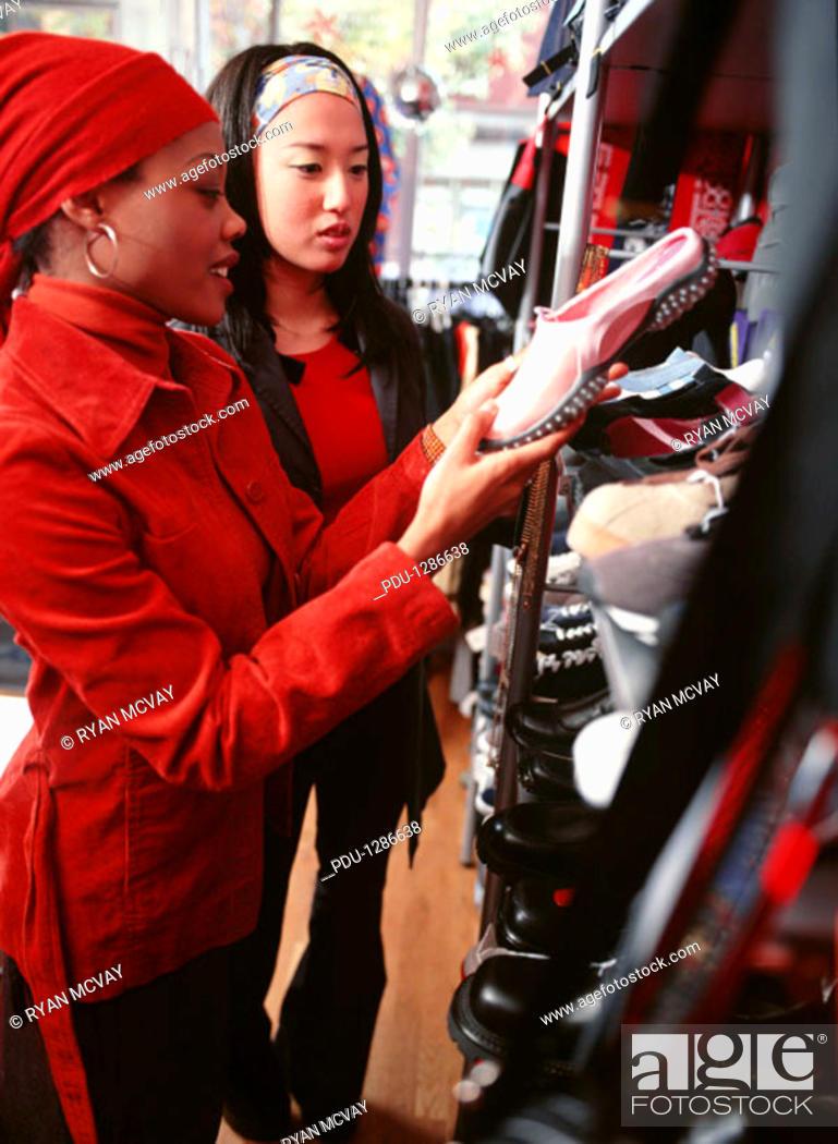 Stock Photo: Two teenage girls (16-17) choosing shoes in shop.