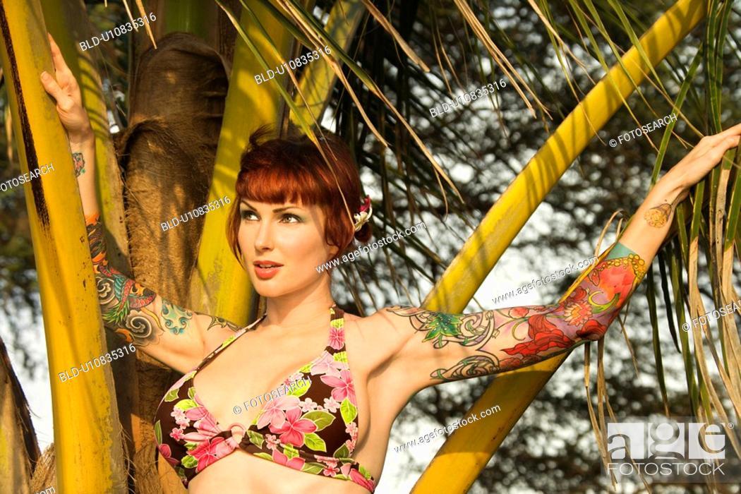 Stock Photo: Woman in bikini with palm tree.