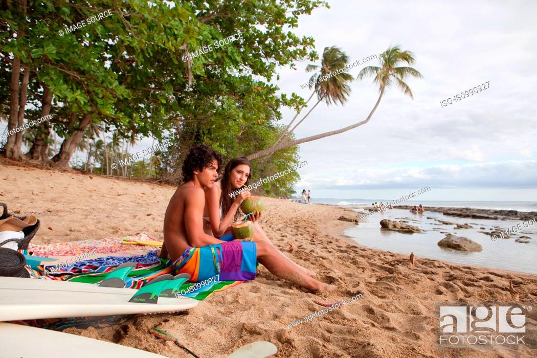 Stock Photo: Young couple sitting on beach drinking coconut milk.