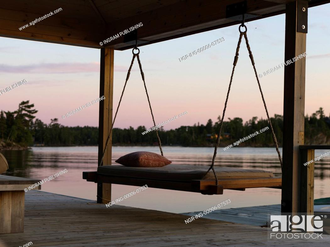 Stock Photo: Swing chair on a dock at sunset, Lake of The Woods, Ontario, Canada.