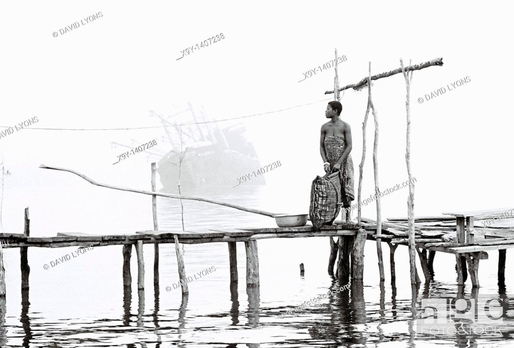 Stock Photo: River Niger delta, Bendel State, Nigeria  Woman on wooden jetty at Bennett Island Anchorage on the Warri River shipping channel.