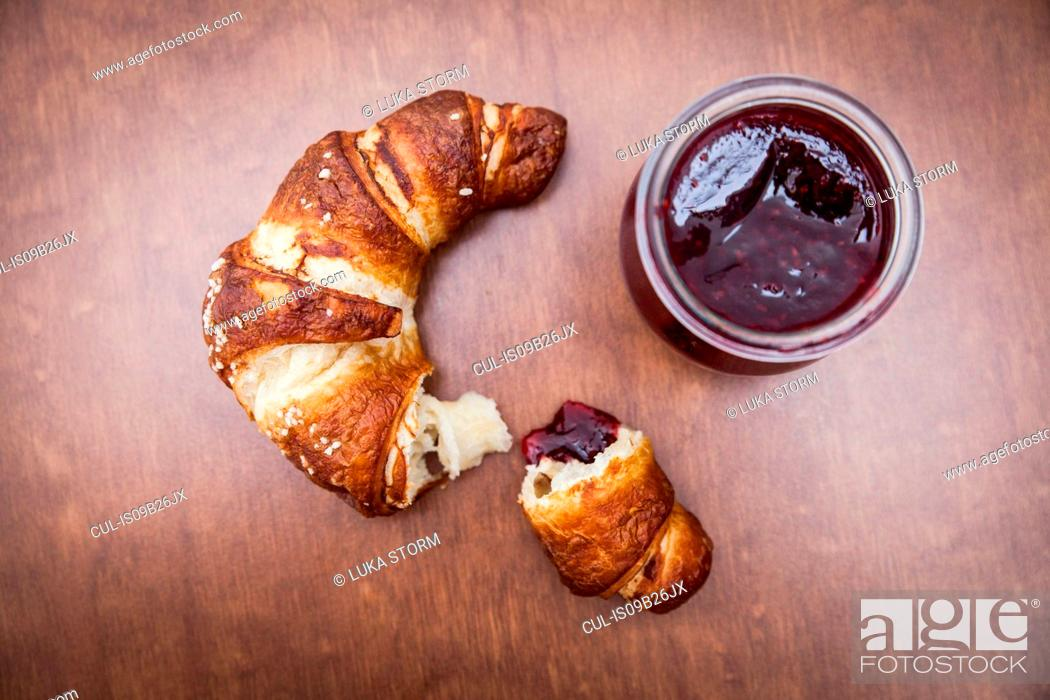 Stock Photo: Broken croissant on wooden table with jam.