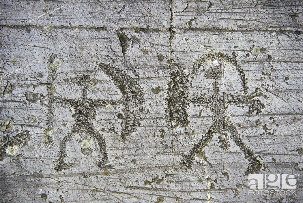 Stock Photo: Prehistoric Petroglyph, rock carving, of two warriors with shileds and a spear carved by the Camunni people in the iron age between 1000-1600 BC.