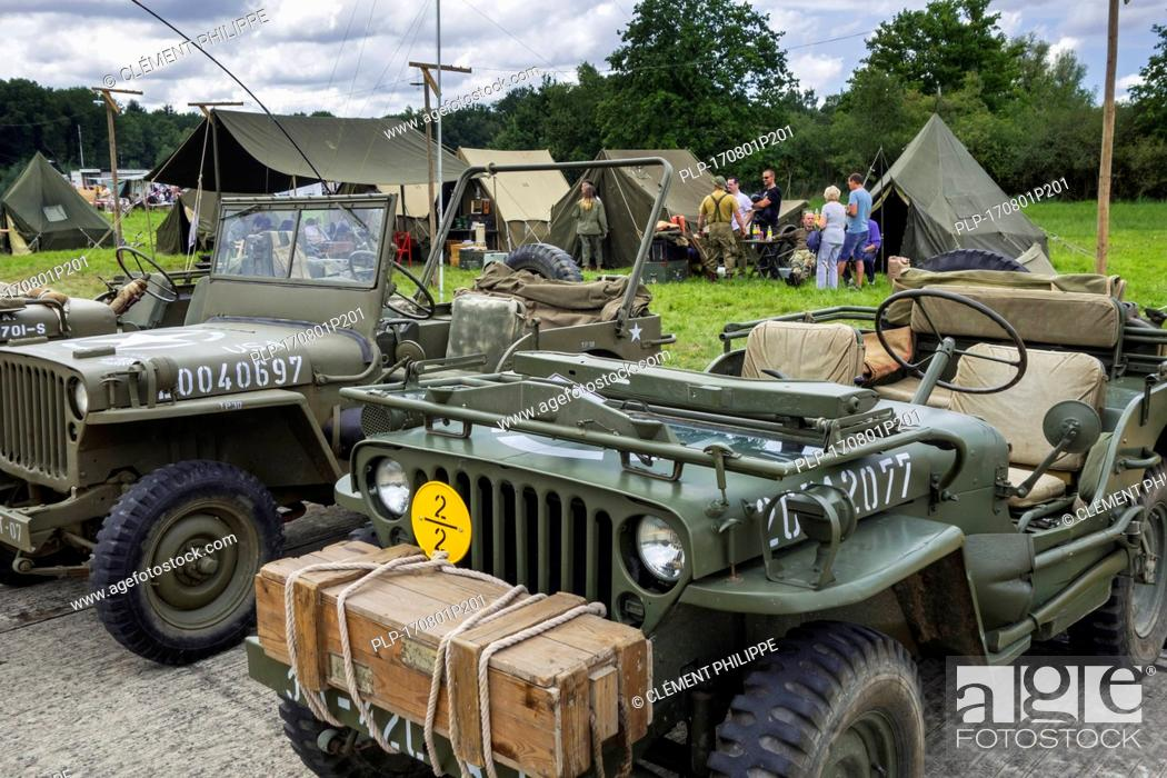 Stock Photo: World War Two US Army Willys MB jeeps, four-wheel drive utility vehicles in front of WW2 reenactors' field camp at militaria fair.