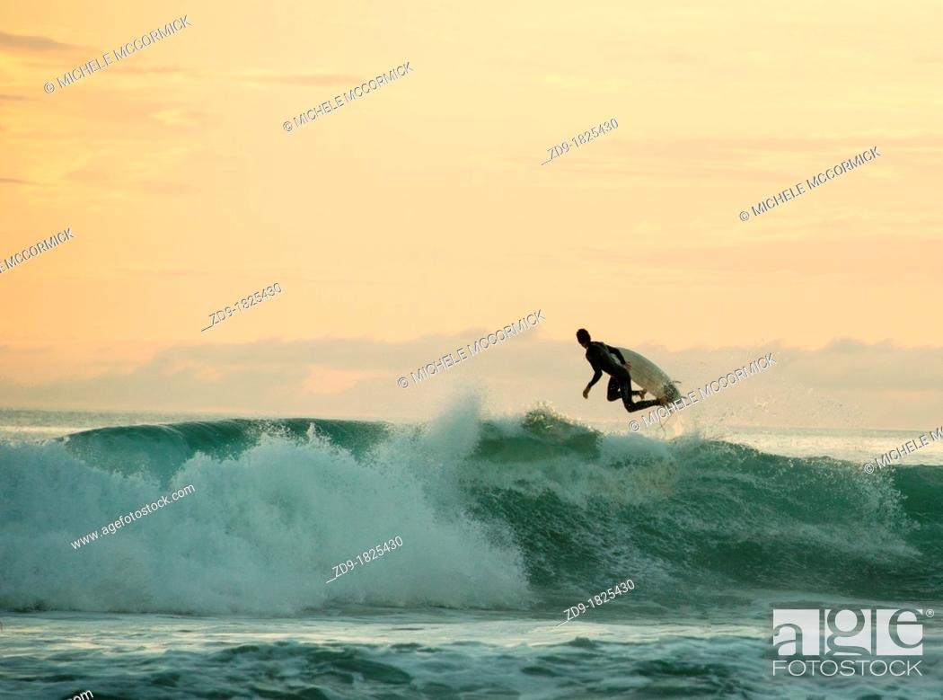 Stock Photo: A surfer leaps back over a breaking wave in the peach-hued sunset.