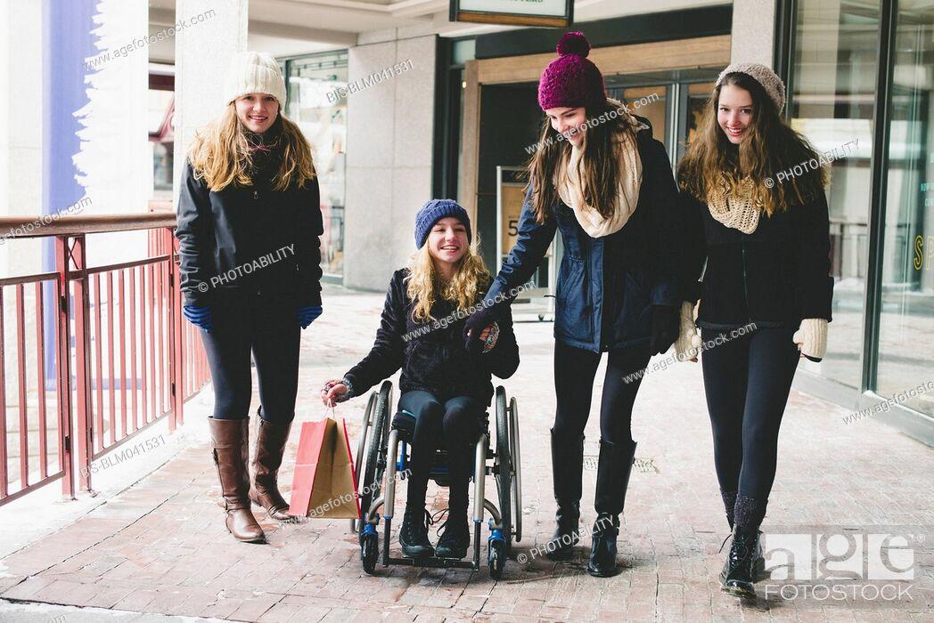 Imagen: Girls walking and using wheelchair on sidewalk.