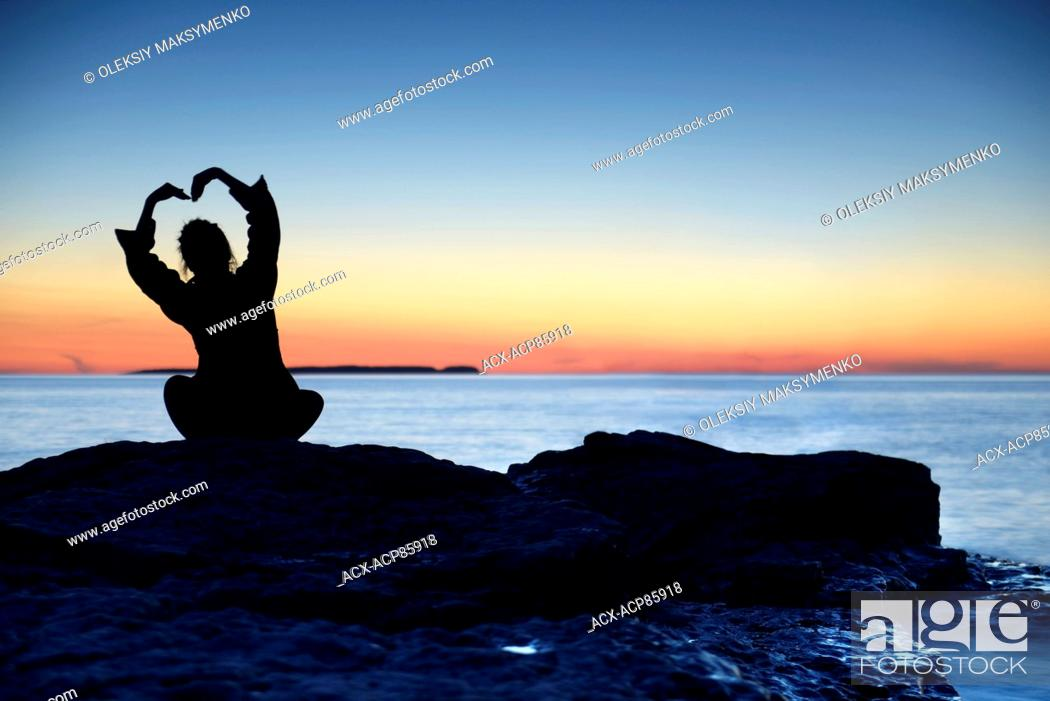 Stock Photo: Silhouette of a woman sitting alone an a shore at sunset with her hands raise in a shape of a flower above her head, conceptual photo.
