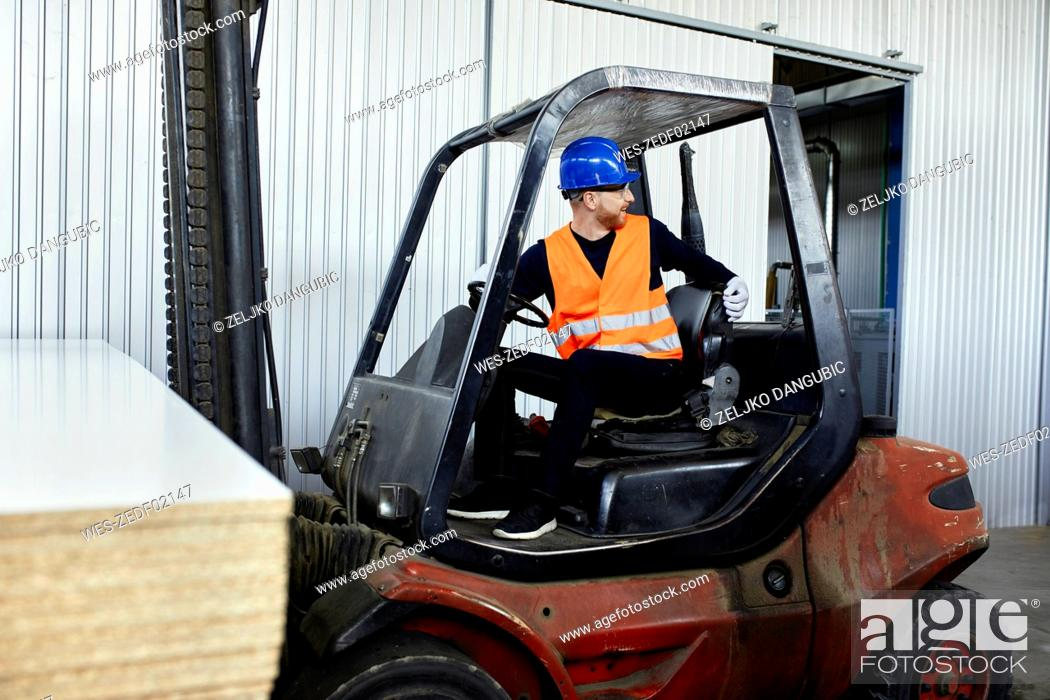 Stock Photo: Worker on forklift in factory turning round.