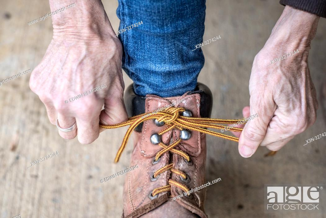 Imagen: Woman's hands pulls her laces tight on her work boots, Fallston, Maryland.