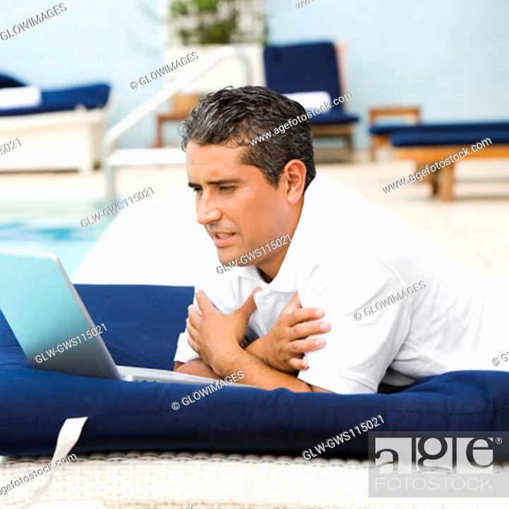 Stock Photo: Side profile of a mid adult man using a laptop.