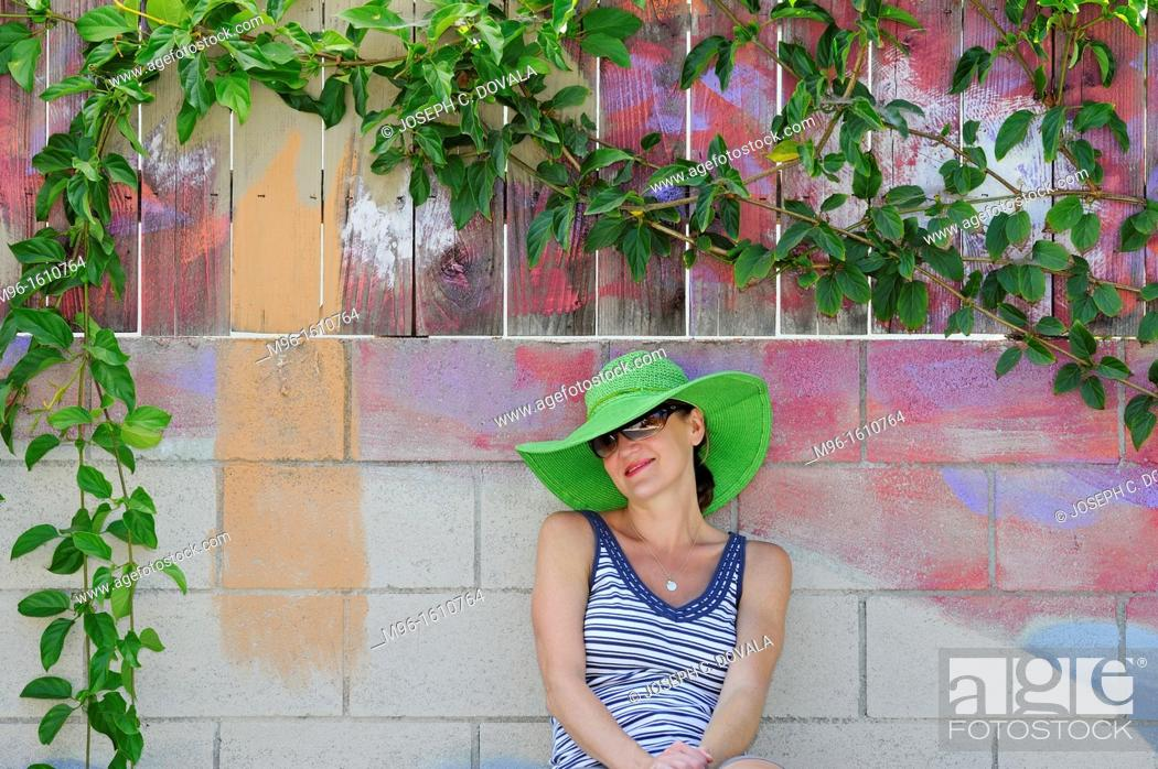 Stock Photo: Woman sitting under painted tree with real leaves, Thousand Oaks, California, USA.