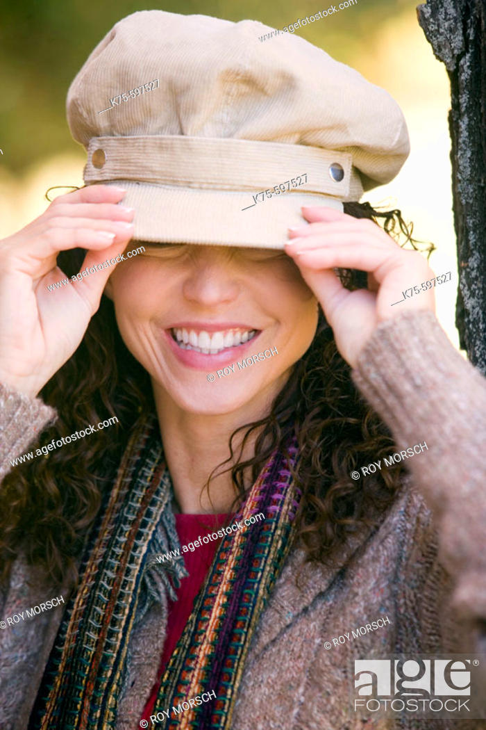 Stock Photo: Woman adjusting her hat.