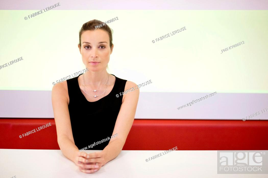 Stock Photo: Portrait of a businesswoman with her hands clasped in an office.
