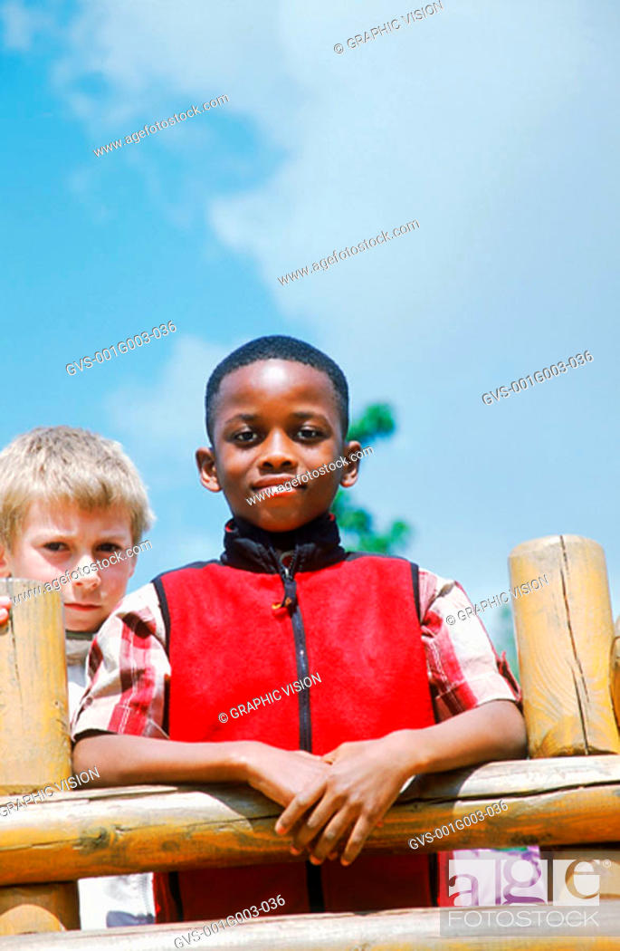 Stock Photo: Young boys against a railing.