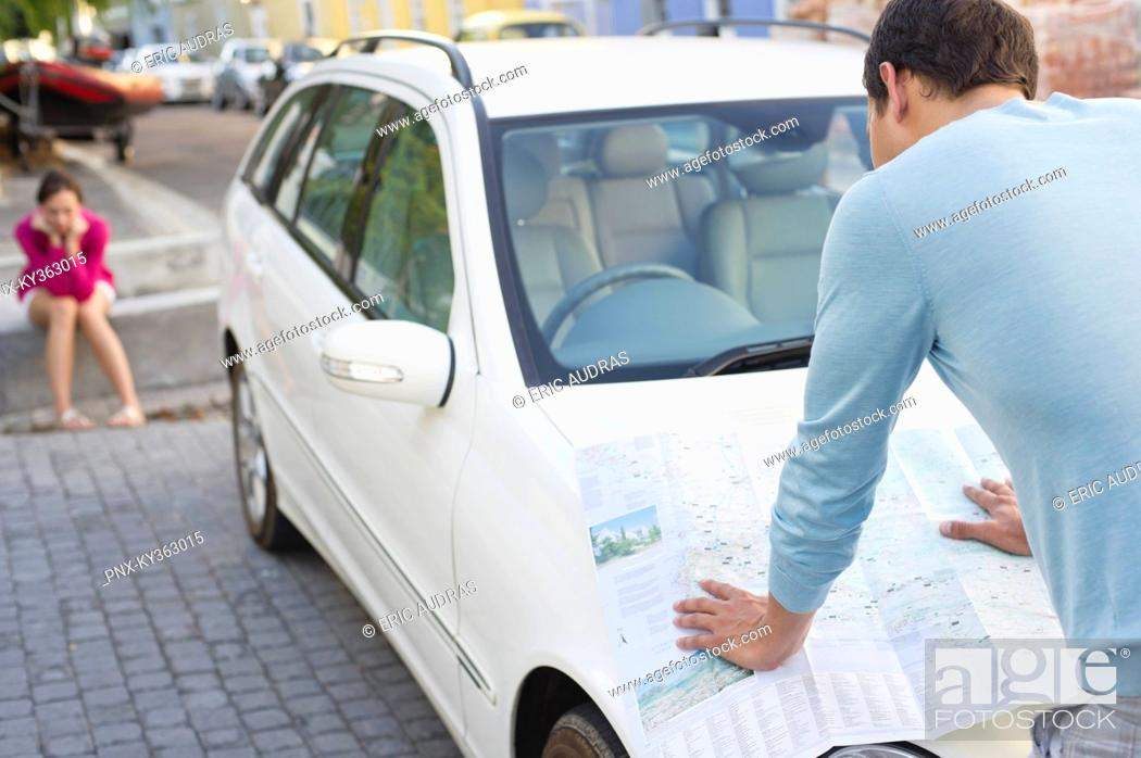 Stock Photo: Rear view of a man looking at map on car with young woman sitting in the background.