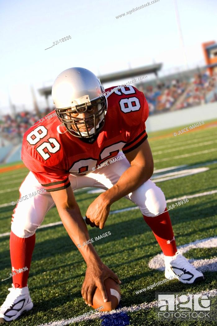 Stock Photo: Center poised to snap football on field.