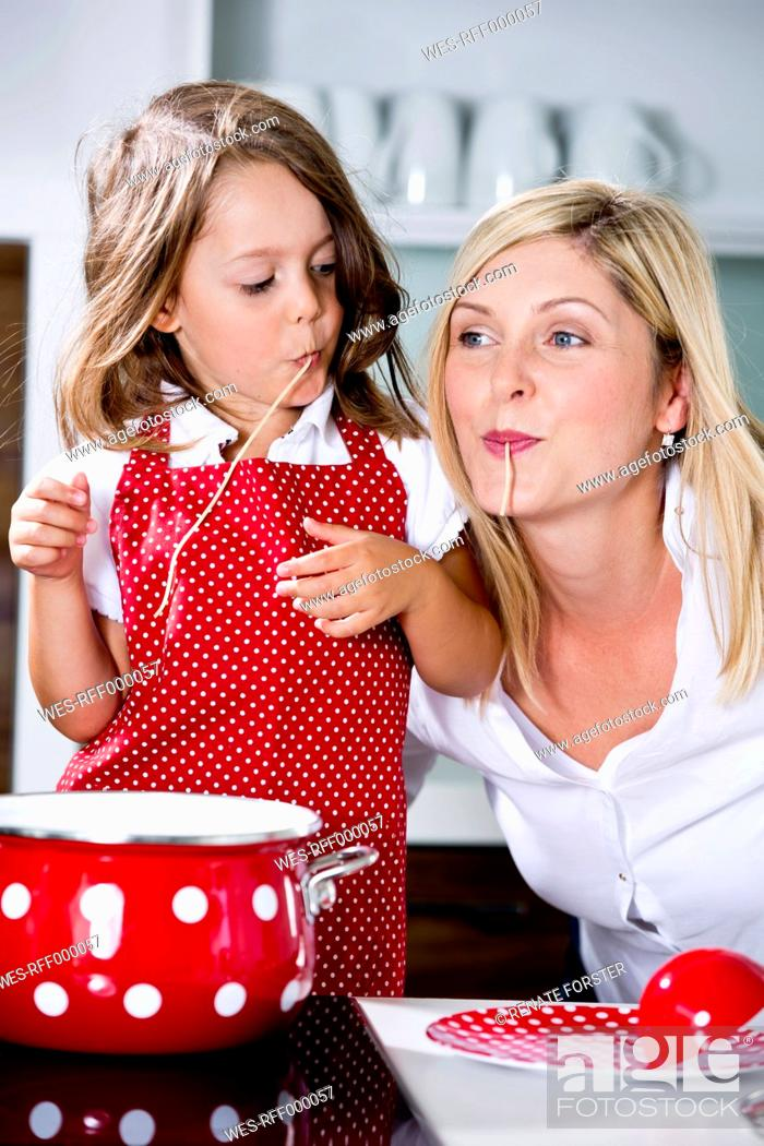 Stock Photo: Germany, Mother and daughter eating noodles in kitchen.
