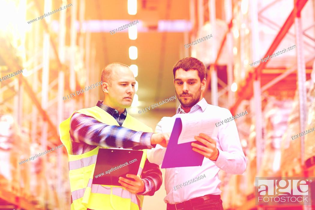 Stock Photo: wholesale, logistic, people and export concept - manual worker and businessmen with clipboards at warehouse.
